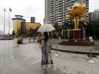 "Visitor stands beside a bronze sculpture called ""Lotus Flower In Full Bloom"", presented by China on Macau's handover in 1999, as Sands Macao is seen in the background, in Macau, China"