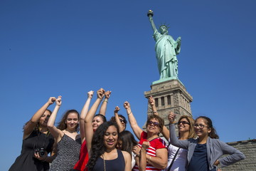 People mimic The Statue of Liberty as they pose for photos in front of it ahead of the Independence Day Holiday in New York