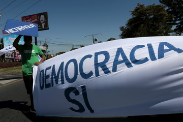 An opposition supporter holds a banner during a protest demanding fairer elections next year, in front of the Supreme Electoral Council (CSE) building in Managua