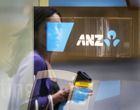 Woman carrying a wallet walks past an ANZ ATM in Sydney