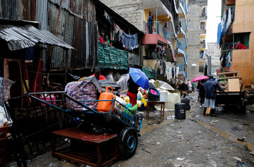 People carry their belongings as they leave the Huruma neighbourhood during the search for residents feared trapped in the rubble of a six-storey building that collapsed after days of heavy rain, in Nairobi, Kenya