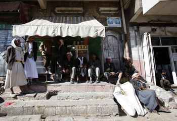 Yemeni workers sit outside a shop at a market in Sanaa