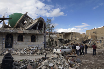 Group of Syrian Free Army activists inspect a damaged mosque at the Sheikh Yassine district area in the eastern city of Deir al-Zor