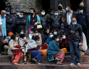 Relatives wait to cremate a family man killed in Saturday's earthquake at Pashupathinath temple in Kathmandu