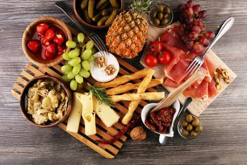 Italian antipasti wine snacks set. Cheese variety, Mediterranean olives, pickles, Prosciutto di Parma over black grunge background