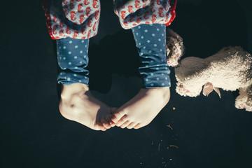 Kinderfüße mit bunter Hose und Kuscheltier im Sommer