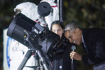 U.S. President Obama looks at moon through telescope with Agatha Sofia Alvarez-Bareiro, a high school senior from Brooklyn, New York, during White House Astronomy Night