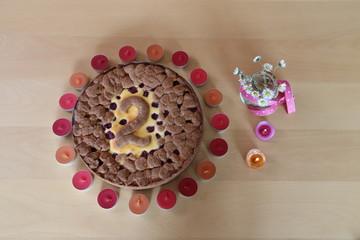 Kuchen dekoriert mit Zahl 2 und Kerzen sowie Gänseblümchen