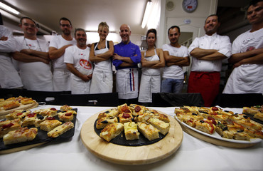 Maurizio Scalia, an Italian chef and teacher at a French pizzaiolo school, poses with adults who attend his training programme in Cap D'Ail