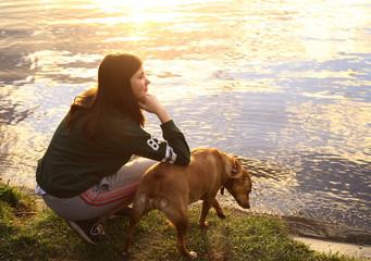 teenage girl with dog on the lake sunset background