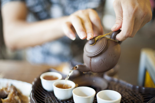 A young man is preparing some hot tea to start his day.