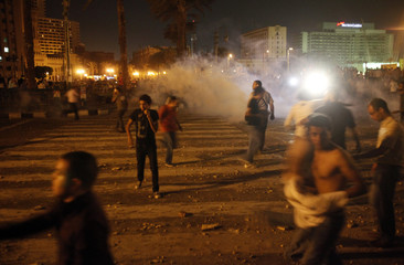 Protesters throw rocks and run away from tear gas in Tahrir Square in Cairo