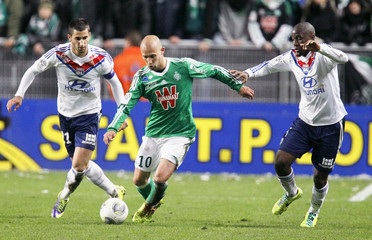 Fofana and Gonalons of Olympique Lyon challenge Cohade of St Etienne during French Ligue 1 match in Saint-Etienne