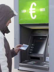 A man withdraws Euro bank notes from ATM in Tallinn