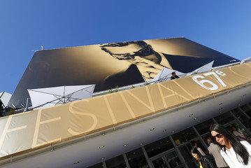 People walk past the Festival Palace which displayed a giant canvas of the official poster of the 67th Cannes Film Festival featuring actor Marcello Mastroianni on the eve of the opening of the Festival in Cannes