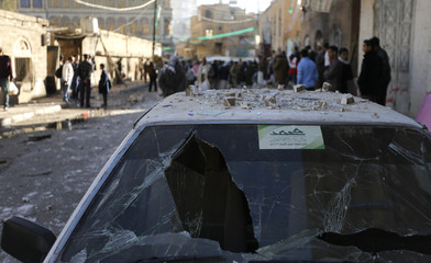 Members of the Shi'ite Muslim Houthi movement and onlookers gather at the site of a blast outside a building belonging to the movement in Sanaa