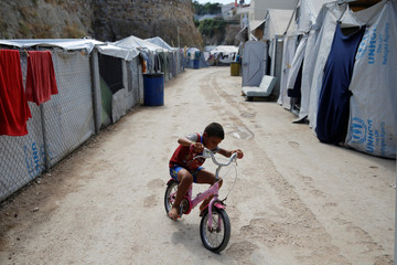 A boy rides a bicycle at the Souda municipality-run camp for refugees and migrants, on the island of Chios
