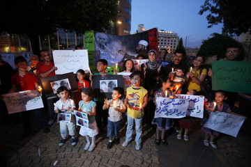Syrian families and their children carry pictures of Syrian boy Hamza al-Khatib and candles during a protest in front of the United Nations building in Beirut