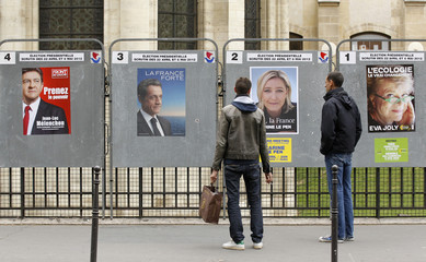 People stop to read the official campaign posters for candidates in the French presidential election in Paris