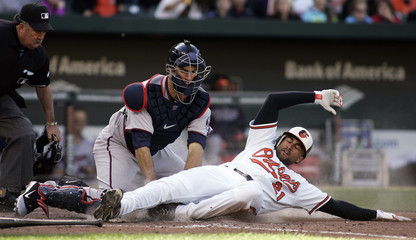 Orioles Nick Markakis is tagged out at home by Twins catcher Joe Mauer during their MLB baseball game in Baltimore
