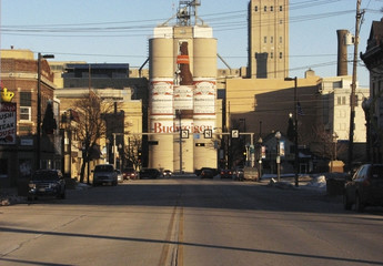 A mural of a Budweiser bottle and two Budweiser cans painted on a malt plant overlooks downtown Manitowoc