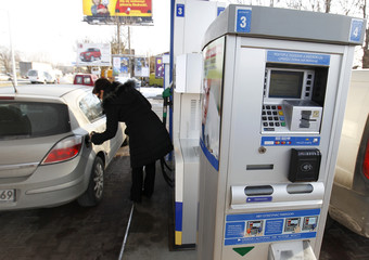 A woman fills up her car with fuel at a Neste gas station in Warsaw