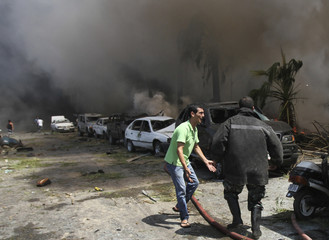 A firefighter rushes to the site outside one of two mosques hit by explosions in Lebanon's northern city of Tripoli