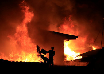 A resident throws a bucket of water at burning shanties at a community of informal settlers engulfed by a fire in Catmon, Malabon city, metro Manila