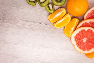 lemon, orange, kiwi, grapefruit, mandarin on a wooden surface. arrangement of sliced fruit. Top view with copy space for text