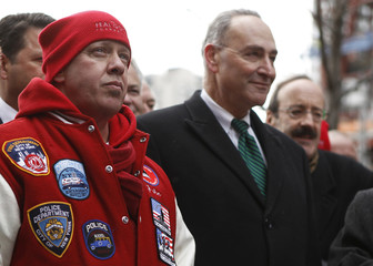 Advocate Feal stands in front of Sen Schumer while attending a news conference celebrating the passage of the James Zadroga 9/11 Health and Compensation Act near Ground Zero in New York