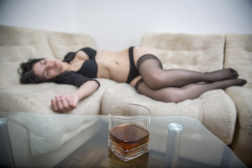 Sexy girl with lingerie sleeping on sofa with glass of alcohol in front of her