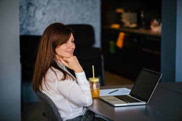 Image of young concentrated woman indoors working with laptop