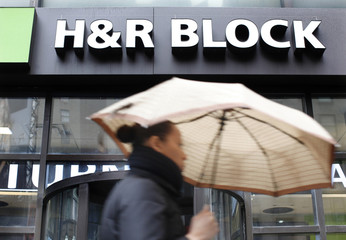 A woman walks past the office of tax preparation company H&R Block, in New York