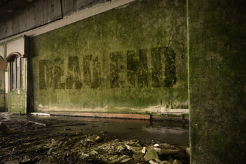text dead end on the dirty old wall in an abandoned ruined house