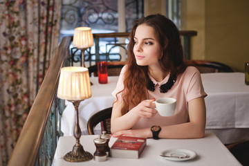 Beautiful young girl sitting alone in a cafe, drinks coffe and h