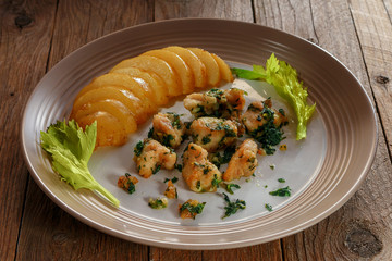 Chicken fillet baked in rice flour, with boiled potatoes in a peel on a crockery plate decorated with celery sprigs