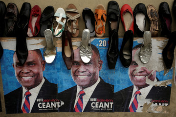 Posters of presidential candidate Jean-Henry Ceant, of Renmen Haiti (Love Haiti) Party, are seen on a wall behind shoes on display for sale in a streett of Port-au-Prince, Haiti