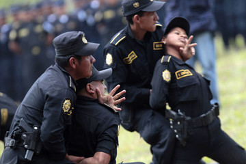 Police officers show immobilisation tactics at SWAT course graduation, in the Mariscal Zavala military base in Guatemala City
