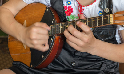 Hands of a musician in a folk costume playing on domra tremolo. Hands of the musician on the move. Selective focus.