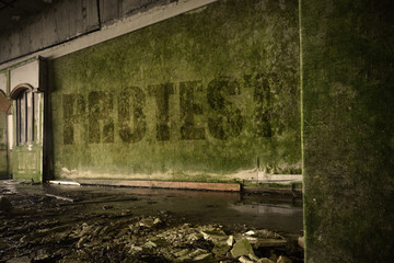 text protest on the dirty old wall in an abandoned ruined house