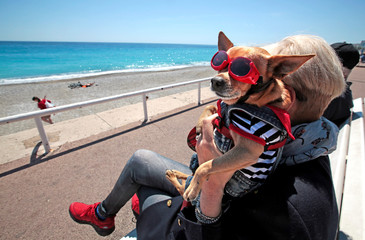 "A woman holds her dog ""Cesar"" as she sits on a bench on the the Promenade Des Anglais in Nice"