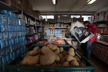 "A volunteer carries a picture of late French comic Coluche as he walks past food in a charity food distribution centre ""Les Restos Du Coeur"" in Nice"