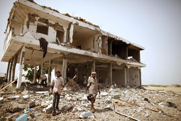 People walk past a building damaged during recent fighting between the army and al Qaeda-linked militants in Zinjibar