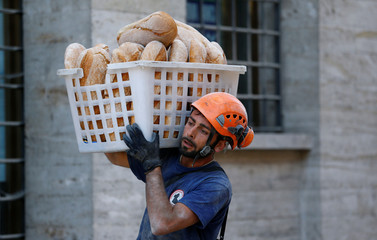 A rescuer carries bread following the earthquake in Amatrice