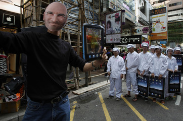 A protester wearing a mask of Apple Inc founder Steve Jobs performs a street drama in Hong Kong