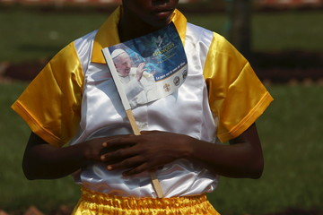 A girl awaits the arrival of Pope Francis at the international airport of the capital Bangui