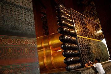 A restorer takes a picture while working at the reclining Buddha feet at Wat Pho temple in Bangkok
