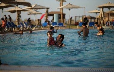 A Palestinian man holding his daughter swims in a pool as they enjoy the warm weather with their family at the Blue Beach Resort in Gaza
