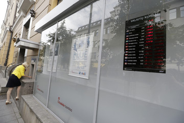 A woman uses an ATM near a bank office with currency exchange rates shown in the window in Vilnius