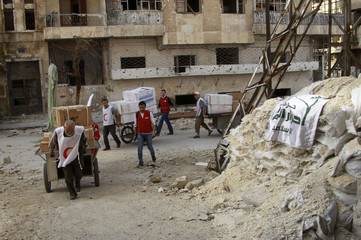 Members of the Syrian Arab Red Crescent move humanitarian and medical aid into rebel-controlled area in Aleppo